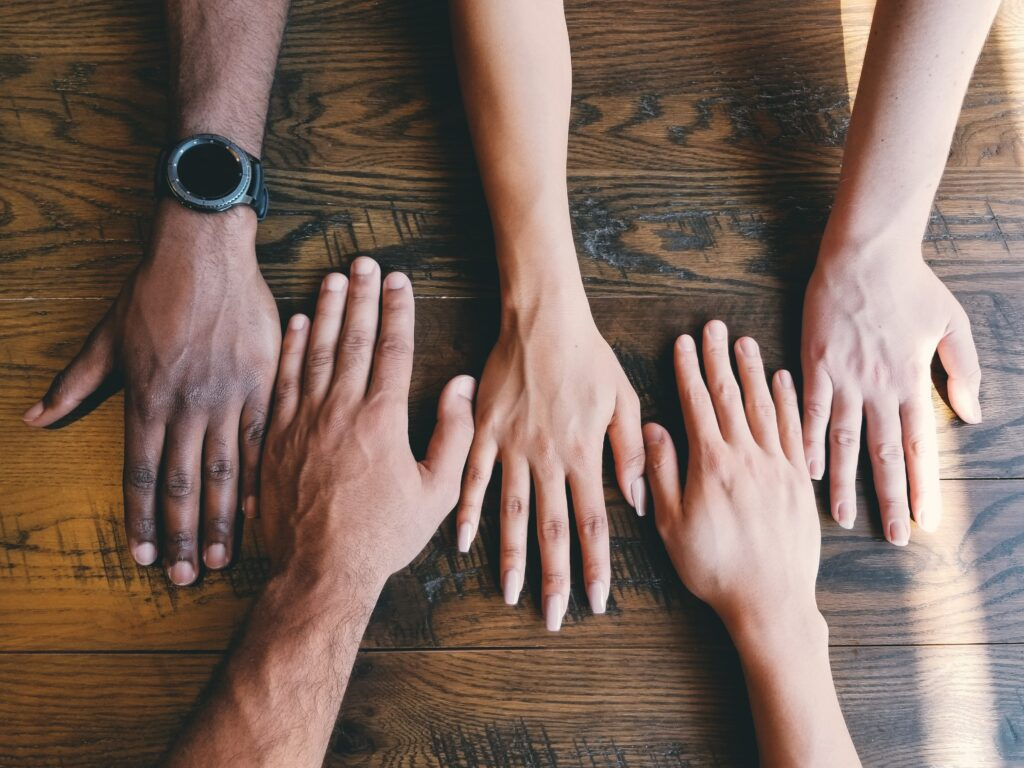 An image of people with their hands together in collaboration!